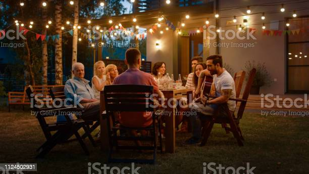Photo of Sitting at the Dinner Table Handsome Young Man Plays the Guitar For a Friends. Family and Friends Listening to Music at the Summer Evening Garden Party Celebration.