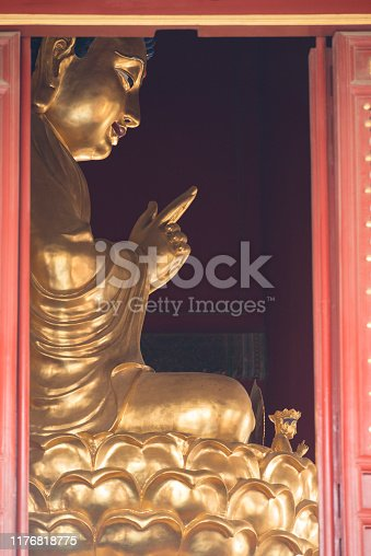 Image of an old traditional gold-painted Buddha figure sitting on a lotus flower inside a small temple or pavilion in a public park near the Forbidden City in Beijing in China.