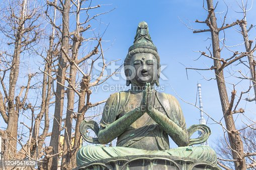 Tokyo, Japan - March 12, 2017 - A statue of a sitting Buddha at Senso-ji Temple. In the distance is the Tokyo Skytree, the second tallest building in the world.