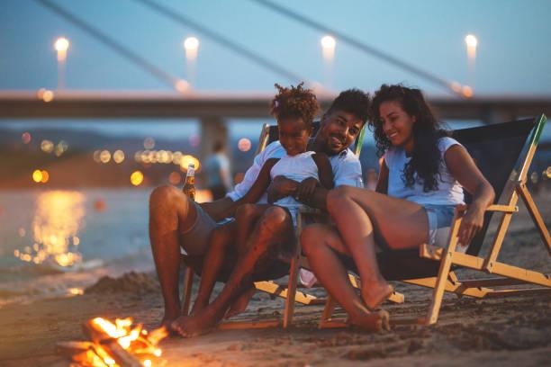 sitting by the camp fire. - falò spiaggia foto e immagini stock