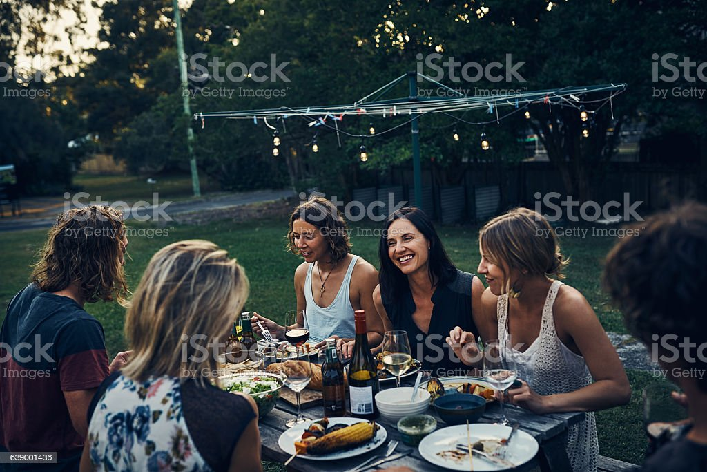 Sitting down with friends and family for a nightly meal - foto de stock