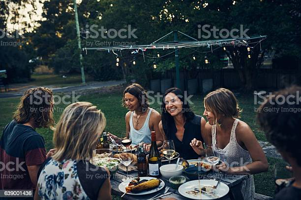 Sitting Down With Friends And Family For A Nightly Meal Stock Photo - Download Image Now