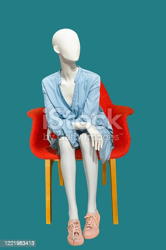 Sitting female mannequin wearing blue casual dress, isolated on blue background. No brand names or copyright objects.
