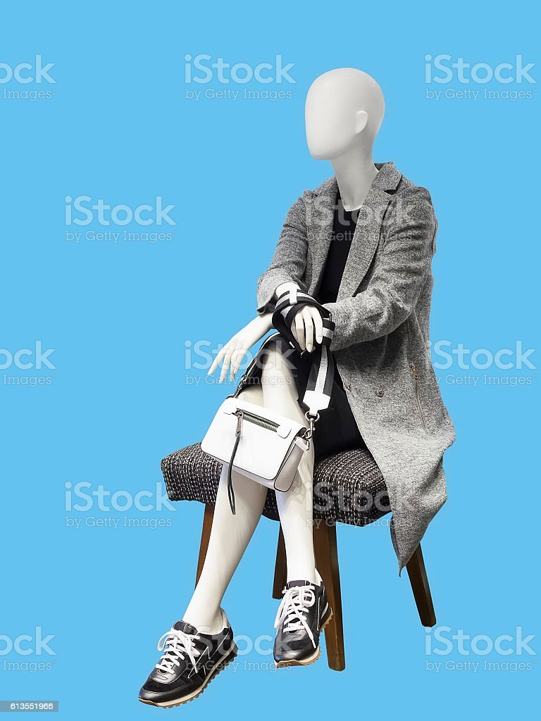 Sitting female mannequin wearing gray coat stock photo