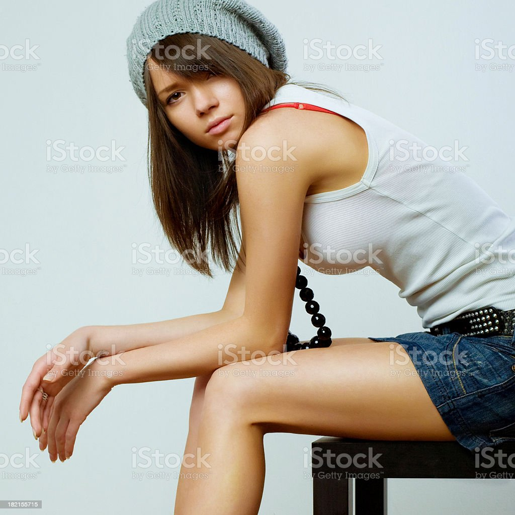 Sitting girl in trendy clothes on off-white background stock photo
