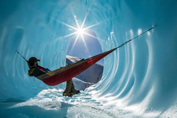 アラスカの氷河にある氷の洞窟の入り口にあるハンモックの中に座っています。 - アイスクライミング ストックフォトと画像