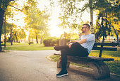 Young man sitting in a park on a bench, on a sunny april day. Wearing sunglasses and a smile.