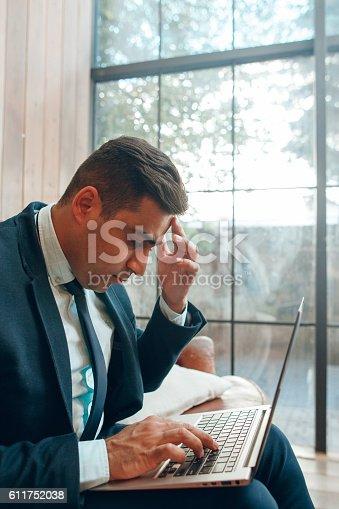 istock Sitting man looking at laptop screen 611752038