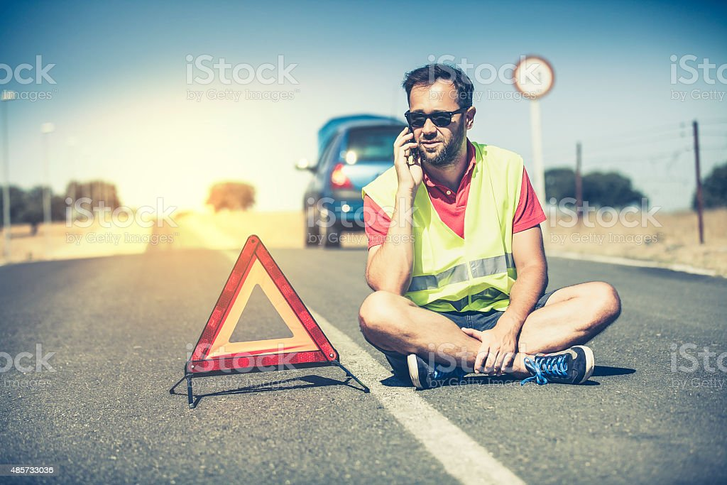 Sitting man talking by phone after car breakdown. stock photo