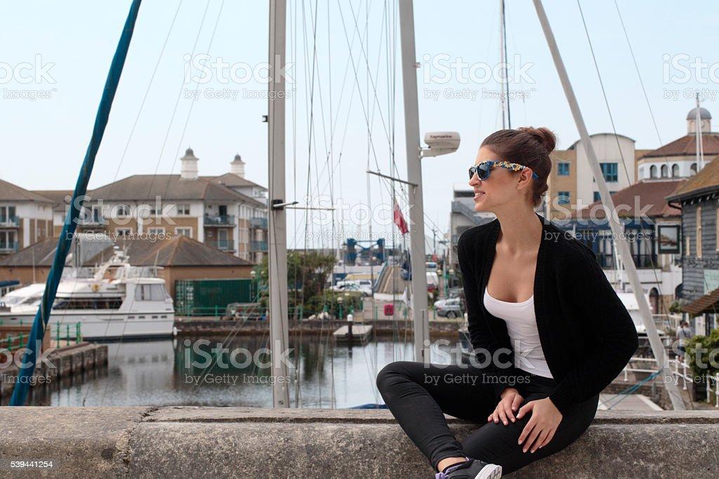 Beautiful Russian outdoor girl model perched on wall Brighton Marina stock photo