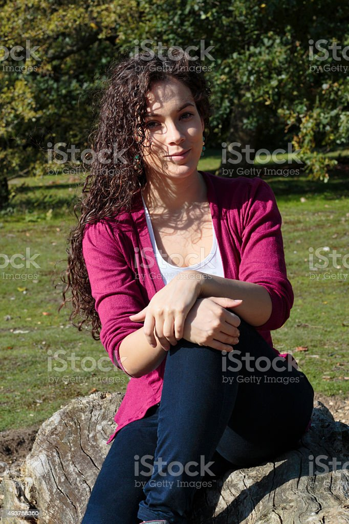 Beautiful Canadian outdoor girl on Mitcham Common sitting on log stock photo