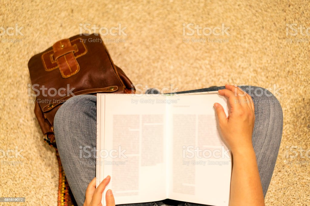 sitting on ground and reading book stock photo
