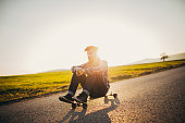 Young man sitting on longboard on the sreet, on a sunny day.