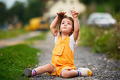Little girl with brown hair outdoors, sitting on the ground and looking up, gesturing