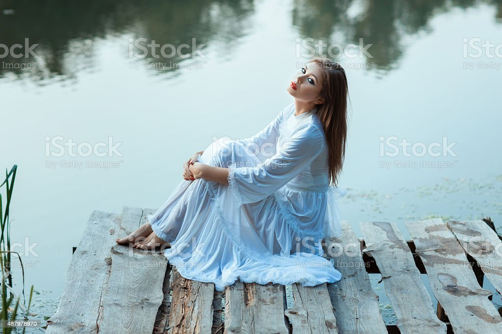 Sitting on the wharf of a beautiful girl. stock photo