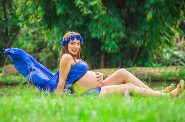 schwangere frau sitzen in einem park mit blauen drees sprengen - drees und sommer stock-fotos und bilder