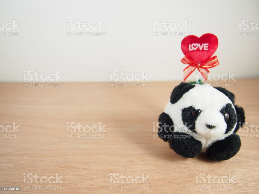 Sitting round fat panda with love tag on red heart pillow stock photo