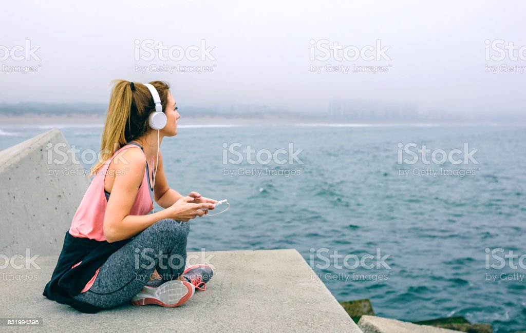 Sitting sportswoman watching the sea stock photo