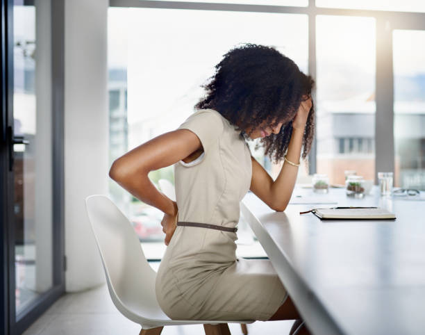 Sitting too long can cause back pain Cropped shot of an attractive young businesswoman suffering with a headache while sitting in her office back pain stock pictures, royalty-free photos & images