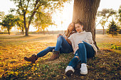 Two young beautiful caucasian women sitting under a tree. Autumn time.