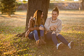 Two young beautiful caucasian women sitting under a tree, talking and laughing. Autumn time.