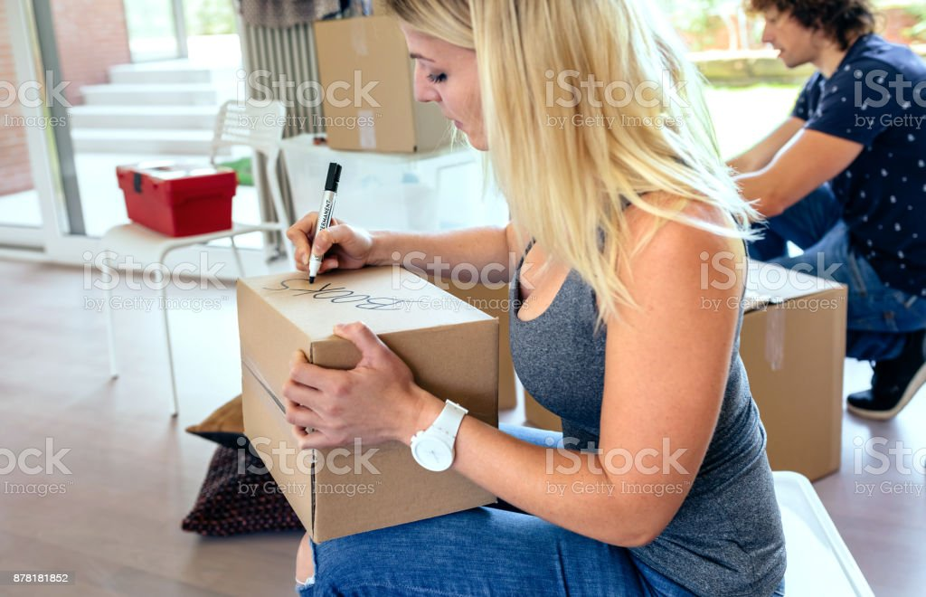 Sitting woman labeling moving boxes royalty-free stock photo