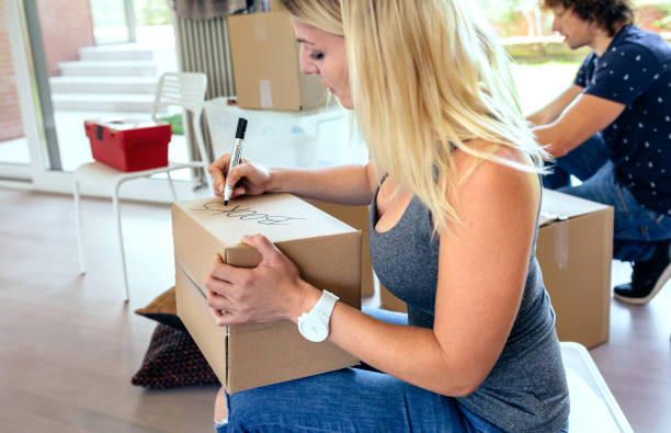 Sitting woman labeling moving boxes Sitting woman labeling moving boxes while her husband prepares boxes labeling stock pictures, royalty-free photos & images
