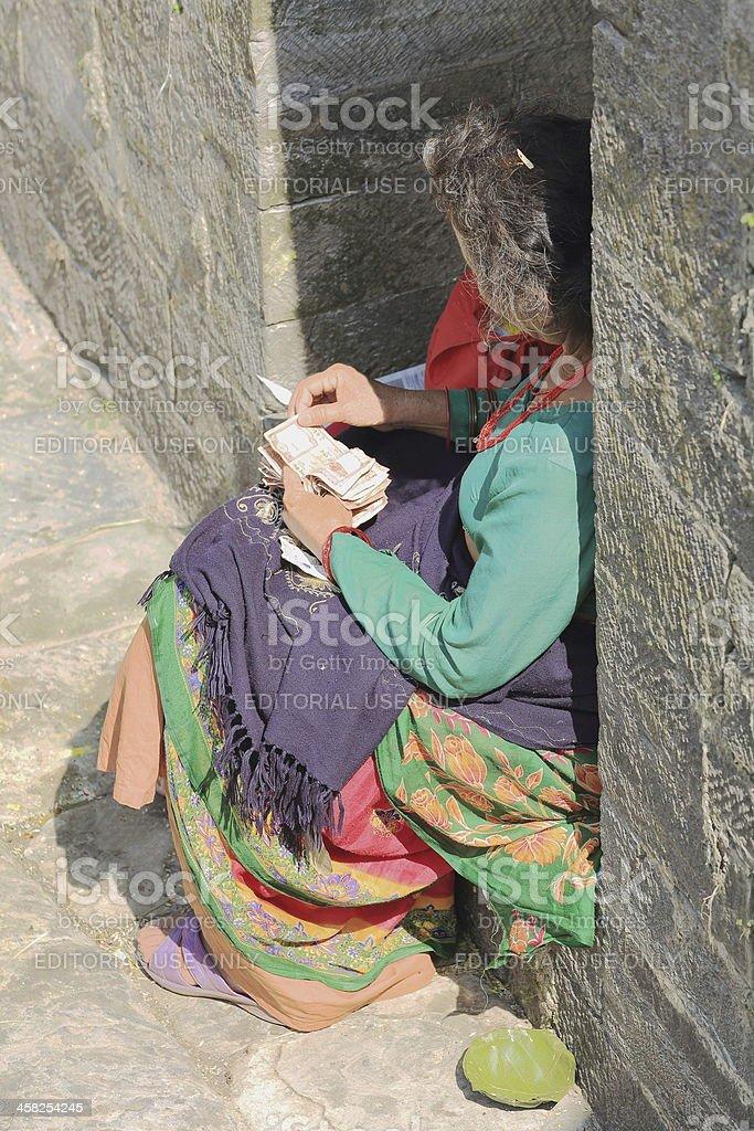 Sitting woman-money counting. Pashupatinath temple-Deopatan-Kathmandu-Nepal. 0291 stock photo