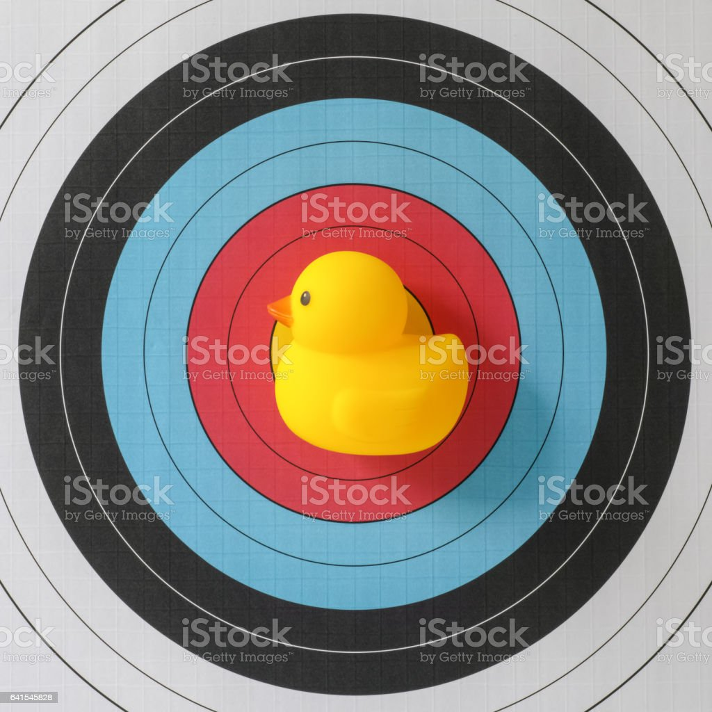 A yellow rubber duck in front of the bull\'s-eye of a sports target,...