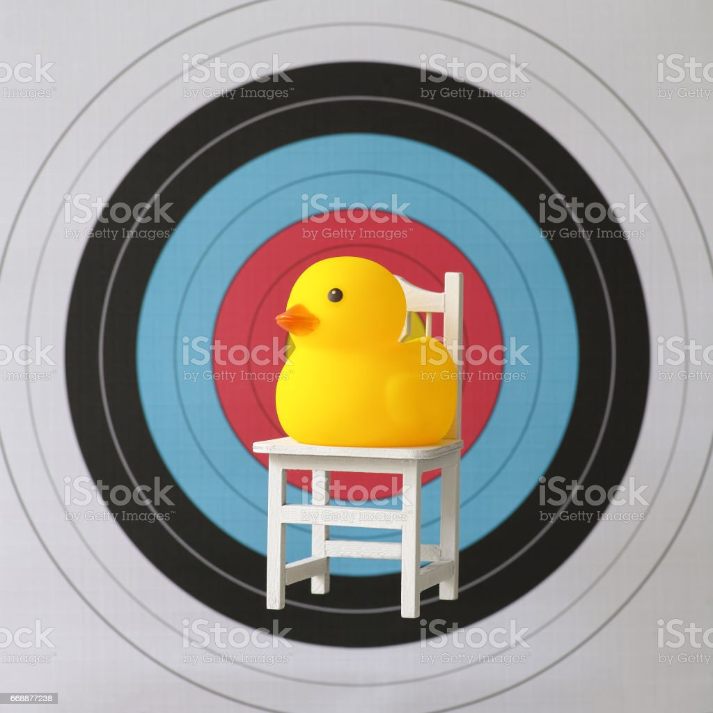 Sitting yellow rubber duck sitting on a chair in front of the bulls-eye of a sports target. stock photo