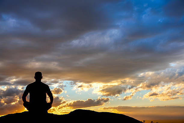 sitting yoga man silhouette watching the sunset sky yoga man silhouette sitting in lotus position watching the sunset sky, sandia mountains, albuquerque, new mexico, horizontal, copy space. new age music stock pictures, royalty-free photos & images