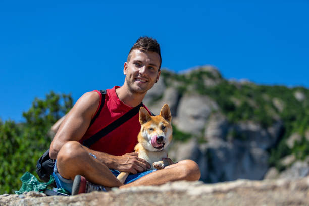 A sitting young man and his dog at the top of Montserrat mountain, Barcelona stock photo