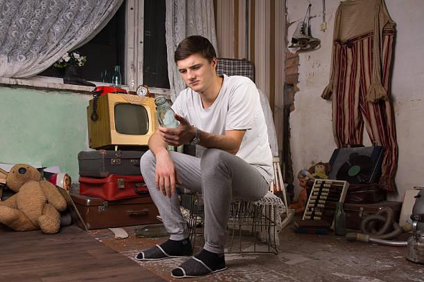 sitzen junge mann hält eine flasche von junk-zimmer - kabelschuhe stock-fotos und bilder