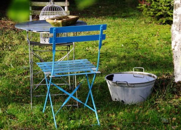 sitzecke im garten mit blauem klappstuhl - bacinella metallica foto e immagini stock