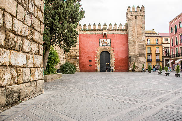 Siviglia, Real Alcazar Seville, Spain - November 14, 2014: Plaza del Triunfo and in the background the entrance of the Real Alcazar, a monument full of history. alcazar palace stock pictures, royalty-free photos & images