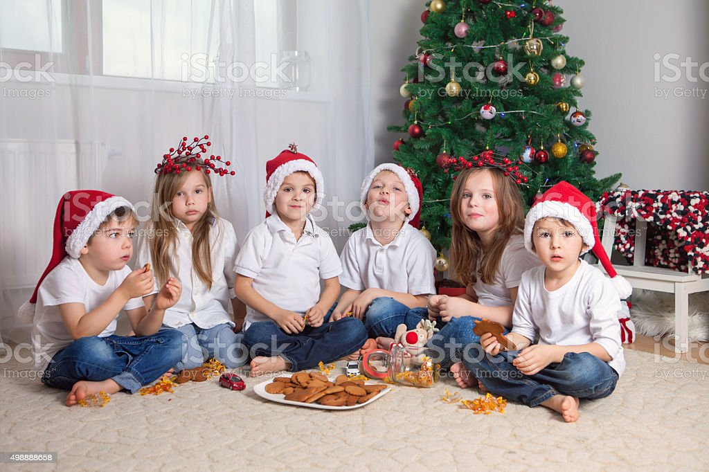 Six adorable children, having fun in front of Christmas tree stock photo