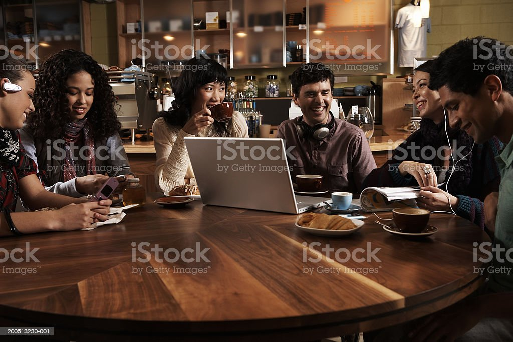 Six adults sitting at table in cafe, talking and laughing royalty-free stock photo