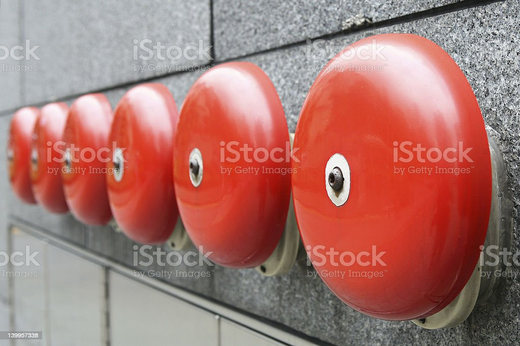 Six aligned red alarm bells on a brick wall stock photo