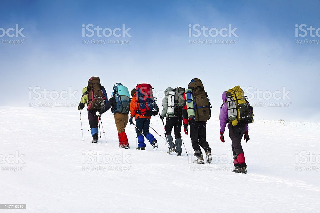 Six backpackers climb a snowy mountain royalty-free stock photo