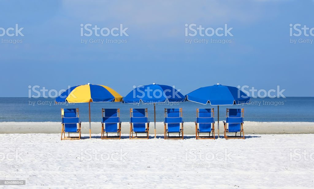 Six beach chairs with umbrellas facing the water's edge stock photo