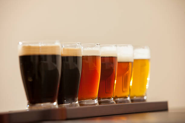 Six beer samples in small glasses on a bar. stock photo