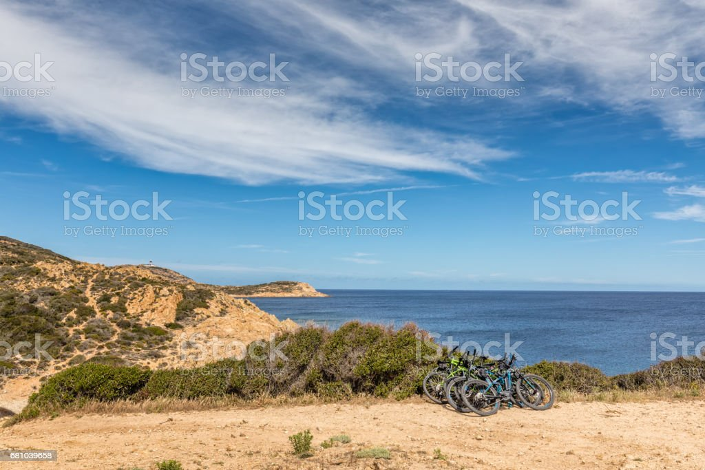 Six bicycles resting on bush on coastal path in Corsica royalty-free stock photo