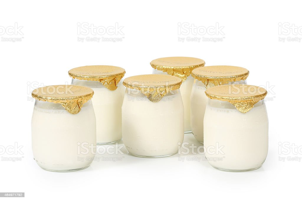 Six bottles of white yogurt with gold foil lids  stock photo