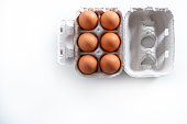 Six Brown eggs on cardboard box gray carton isolated on white background