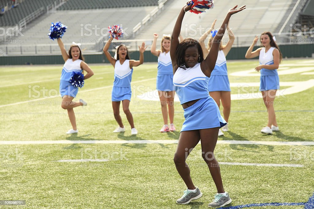 Six cheerleaders practicing on a football field. stock photo