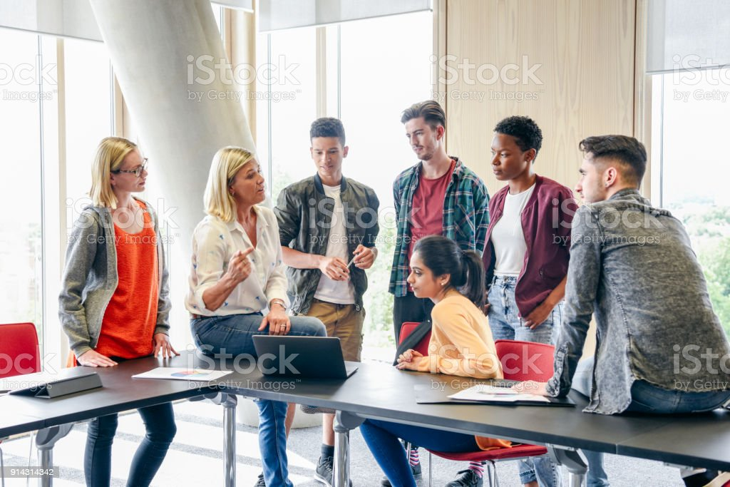 Six college students listening to mature female lecturer with laptop in classroom stock photo