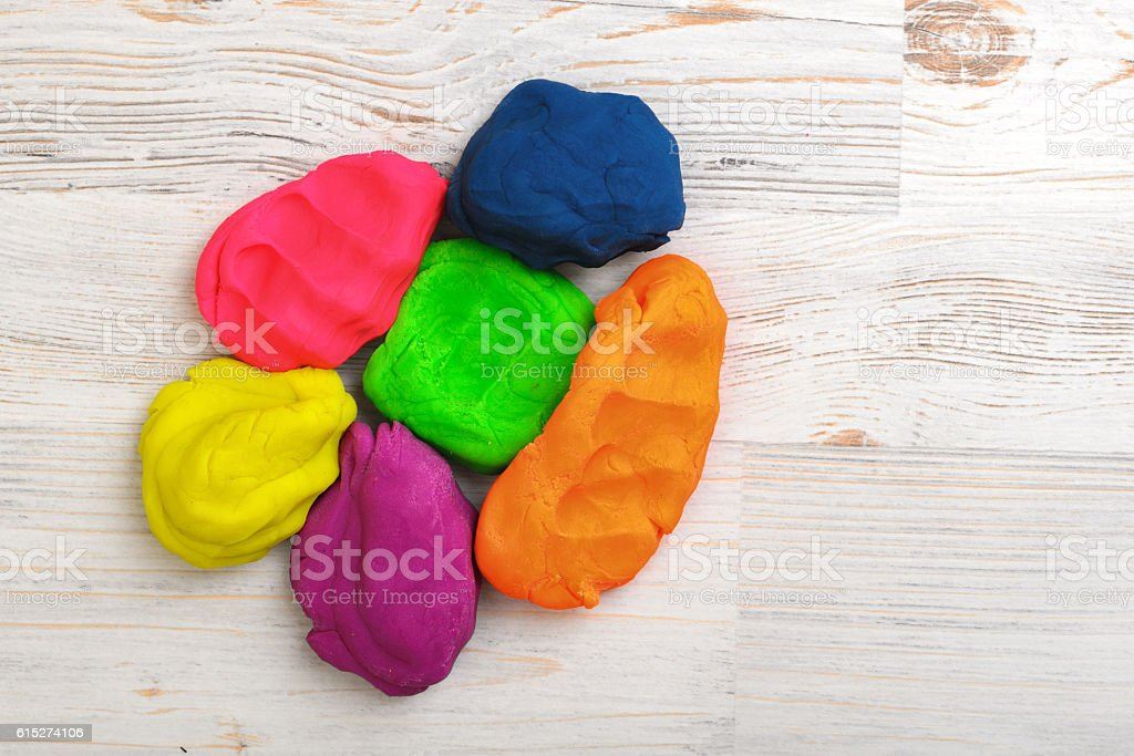 Six colorful lumps of crumpled plasticine put together on a stock photo