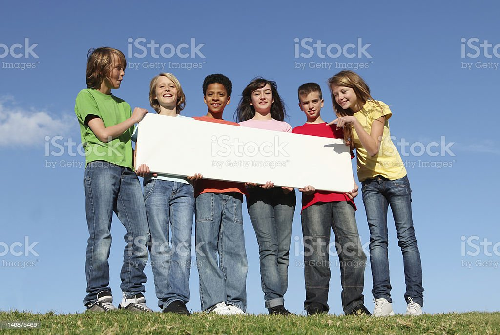 Six diverse kids holding a blank white sign stock photo