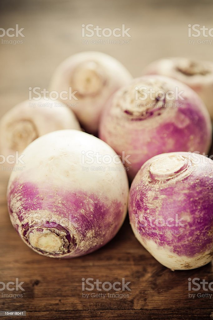 Six dusty turnips on a wood surface stock photo