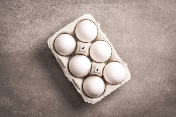 Six eggs in paper container box. stock photo